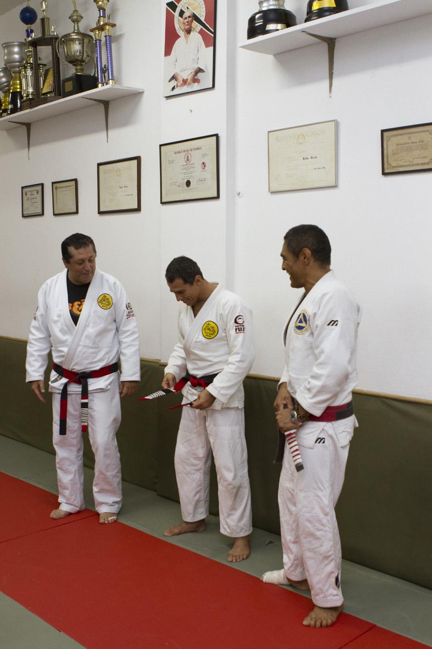 Royler ajusta a faixa-coral de Jiu-Jitsu após recebê-la dos irmãos Rolker e Rickson.