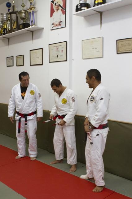 Royler ajusta a faixa-coral de Jiu-Jitsu após recebê-la dos irmãos Rolker e Rickson