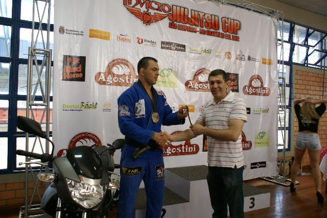 Alexandre Ceconi ganha a chave da motocicleta das mãos do organizador do evento, Válerio Doca. Foto: Divulgação