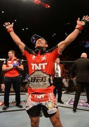 Aldo ergue os braços após receber o cinturão de Dana. Foto: UFC/Facebook