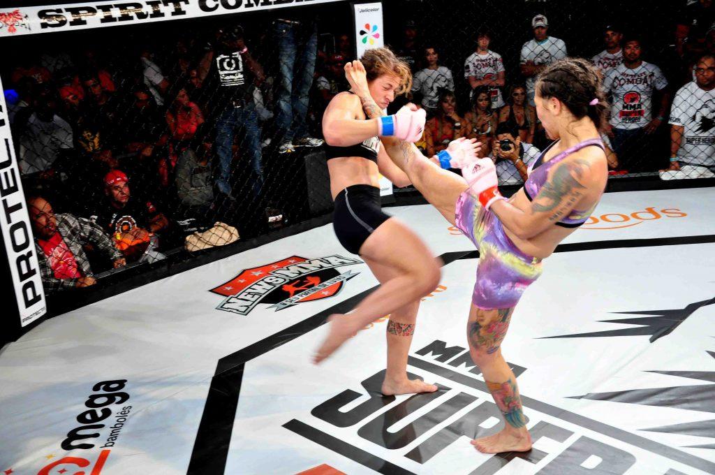 Karina acerta chute em Hellen no caminho do cinturão do MMA Super Heroes. Foto: Dene Sampaio/Divulgação