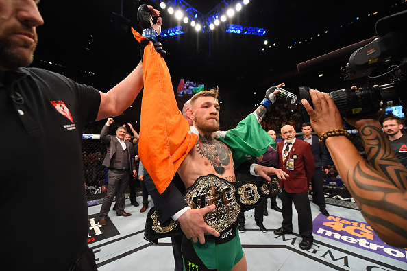 McGregor recebe o cinturão das mãos de Dana White. Foto: Josh Hedges/Zuffa LLC via Getty Images