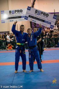 Otavio e Tinoco com seus cheques de premiação no NY BJJ Pro. Foto: IBJJF/Facebook